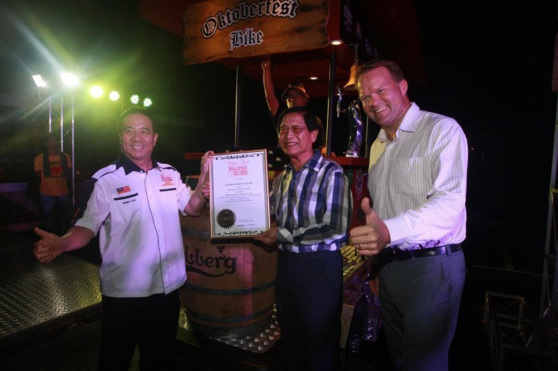 """YBhg Tan Sri Danny Ooi [left], Founder of the Malaysia Book of Records, presented Carlsberg Malaysia's Chairman of the Board Dato' Lim Say Chong [middle] and Managing Director Henrik Juel Andersen [right] with the award for Malaysia's """"First 6 Pedalist Beverage Cart""""."""